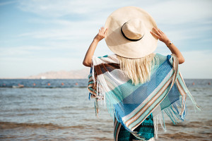 Back view of woman in beachwear and hat which standing on the beach and looking away