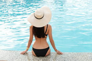 Back view of woman in swimsuit and hat which sitting near the pool