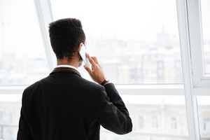Back view of Young African business man in black suit talking on phone and looking at window