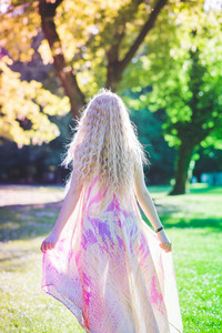 Back view of young beautiful blonde hair woman wearing pink dress standing in the forest - adventure, magic, dreamy concept
