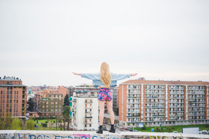 Back view of young beautiful caucasian blonde girl with arms wide open feeling free with city in background - freedom, satisfaction, emancipation concept