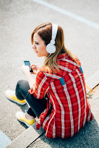 Back view of young beautiful caucasian blonde hair woman listening music with headphones and smart phone hand hold outdoor in the city - music, technology, communication concept