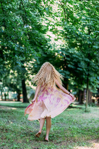 Back view of young beautiful caucasian blonde long hair woman playing in the forest wearing long pink dress - moving, freedom, serene concept
