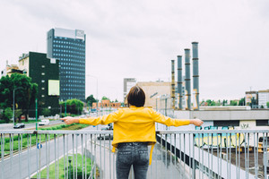 Back view of young beautiful caucasian brown girl with arms wide open with city on background, feeling free in the suburbs - freedom, satisfaction, future, girl power, emancipation concept.