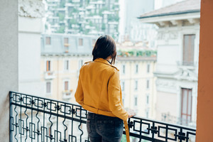 Back view of young beautiful caucasian brown hair woman leaning on handrail overlooking pensive - melancholy, thoughtful, thinking future concept