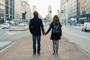Back view of young beautiful couple in love hand in hand walking outdoor in the city, having fun - first date,  romantic, love concept