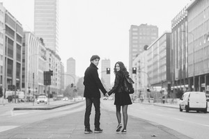 Back view of young beautiful couple in love walking outdoor in the city, having fun, turnink looking at camera - first date,  romantic, love concept. Black and white.