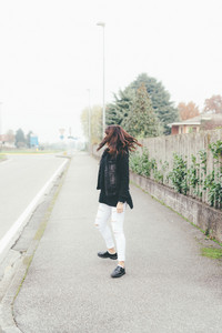 Back view of young beautiful eastern woman wearing hoodie walking outdoor in the city - walking, strolling, autumn concept