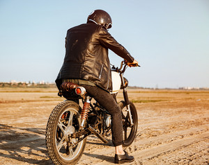 Back view of young brutal man in a black jacket and glasses driving retro motorcycle
