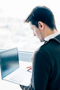 Back view of young contemporary businessman standing near window using a notebook hand hold - business, work, multitasking concept