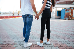 Back view of young couple in love standing together outdoors