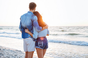 Back view of young couple standing at sunrise on the beach