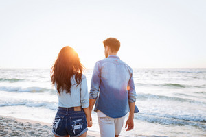 Back view of young couple walking at sunrise on the beach