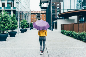 Back view of young woman walking outdoor in rainy day - rainy, weather, leaving concept