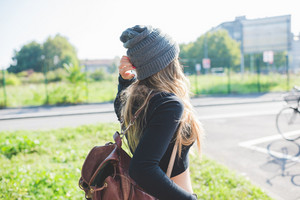 Back view of young woman wearing hat and backpack walking outdoor in city backlight -