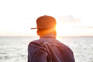 Back view photo of attractive african man wearing cap and dressed in jeans jacket looking at beach.