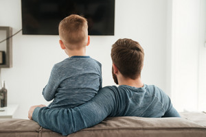 Back view photo of father watching TV with his little cute son.