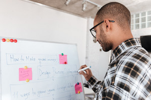Back view photo of young african businessman wearing glasses in office working with flipchart.