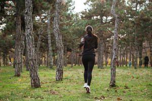Back view photo of young woman runner in warm clothes and earphones running in autumn park