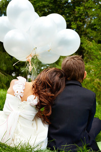 Backs of children bride and groom with balloons sitting in park