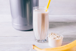 Banana, protein shake in a glass and scoop on white wooden table close-up