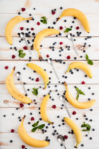 Bananas, berries and spoons on wooden background