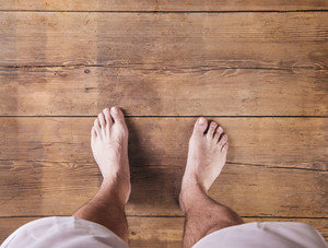 Bare feet of a runner on a wooden floor background