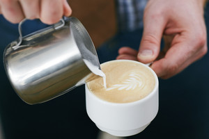 Barista adding cream or milk into cup of latte
