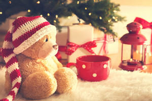 Bear wearing Santa hat with Christmas gift boxes on a white carpet at night