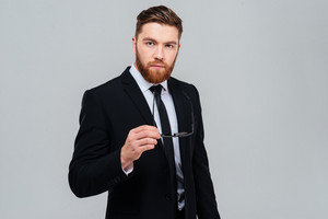 Bearded business man in black suit holding his glasses in hand and looking at camera. Isolated gray background