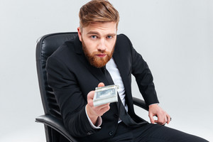 Bearded business man in black suit holding money in one hand and sitting on armchair as well as looking at camera. Isolated gray background