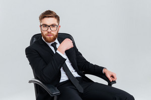 Bearded Business man in glasses and black suit sitting on armchair and looking at camera. Isolated gray background