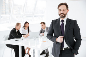 Bearded Business man in office with colleagues by the table on background