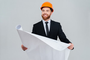 Bearded happy engineer in black suit and orange helmet with open layout looking aside. Isolated gray background