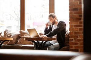 Bearded man sitting by the table in cafe with laptop and coffee with window on background