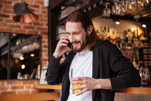 Bearded man talking on phone with cup of beer and standing near the bar