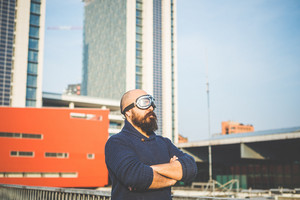 bearded man with glasses aviator in the high city