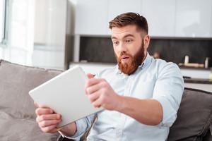 Bearded man with tablet on sofa. so funny man