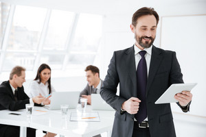 Bearded Smiling Business man looking at tablet in hands in office with colleagues on background