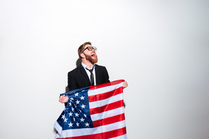 Bearded young Business man in suit and glasses holding USA flag and looking up. Isolated gray background