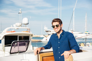 Bearded young handsome man wearing sunglasses and standing on a yacht