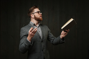 Bearded young man in eyeglasses and casual suit reading book and gesturing with hands isolated on the black wooden background