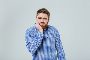 Bearded young man standing and having toothache
