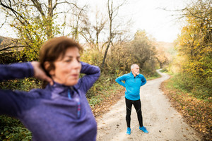 Beautiful active senior couple running together outside in sunny autumn forest, stretching