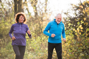 Beautiful active senior couple running together outside in sunny autumn forest