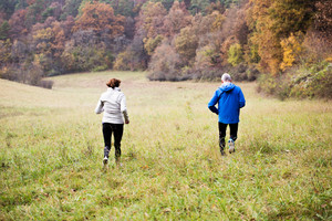 Beautiful active senior couple running together outside in sunny autumn nature, rear view