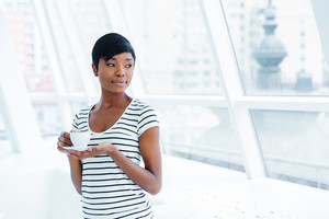 Beautiful african american young businesswoman standing and drinking coffee in office