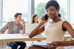 Beautiful african american young businesswoman working with colleagues and talking on cell phone in office