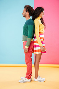Beautiful african young couple standing back to back over colorful background