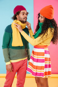 Beautiful african young woman in hat and scarf taking care of her boyfriend over colorful background